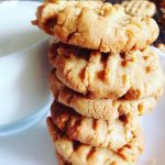 3 ingredient peanut butter cookies stacked next to a glass of milk
