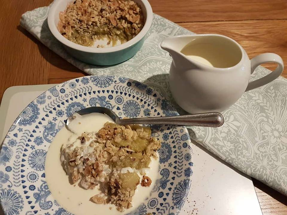 low carb rhubarb crumble and double cream in a bowl