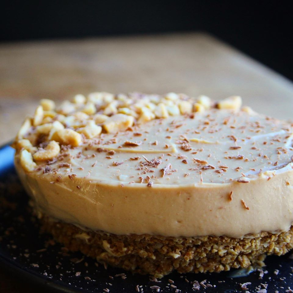 Peanut butter tart with crushed peanuts on top, sitting on a black plate