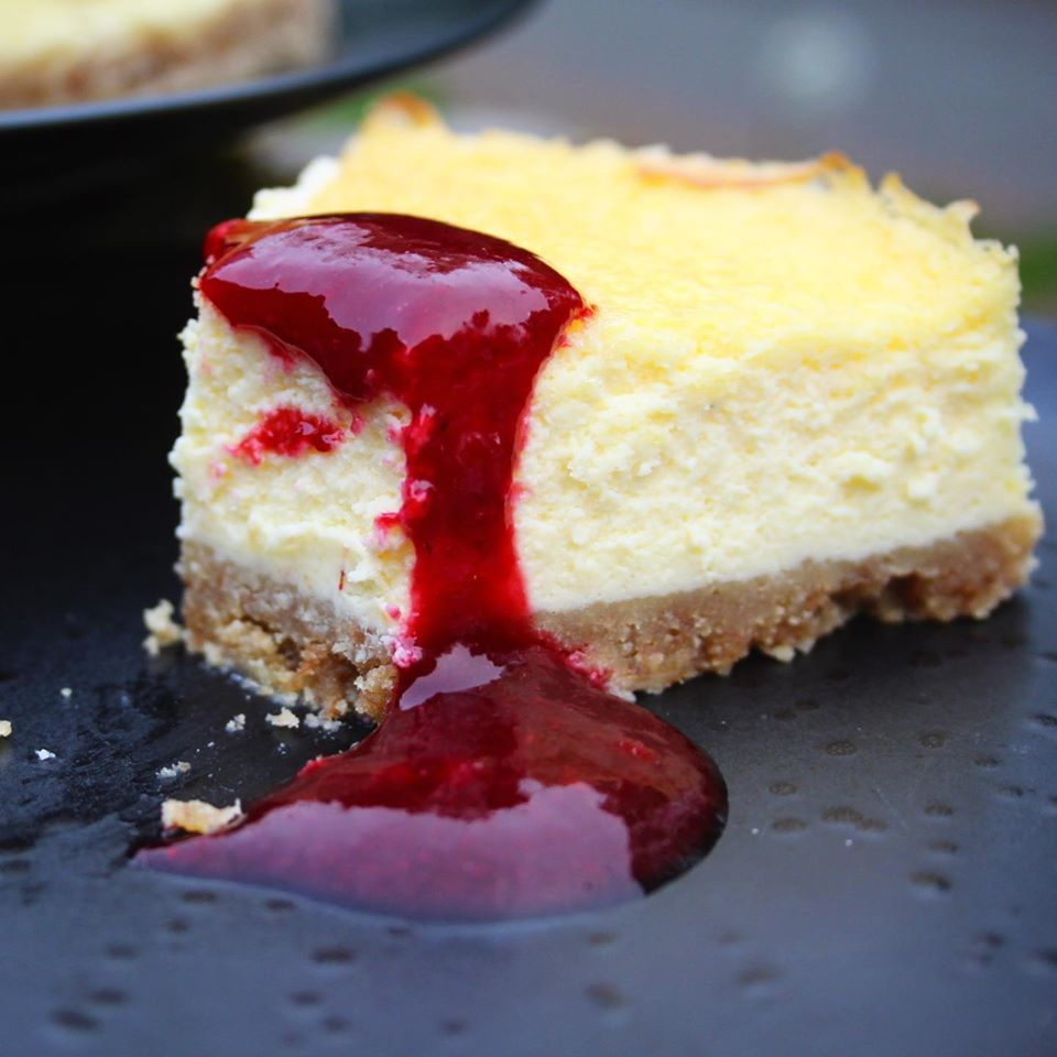slice of baked cheesecake with raspberry sauce drizzled on top