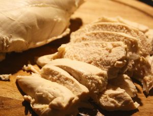 poached chicken sliced on wooden chopping board